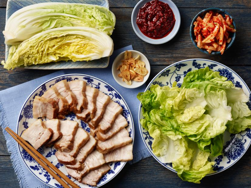A selection of boiled pork, lettuce, and sauces that make up bossam, a traditional Korean dish