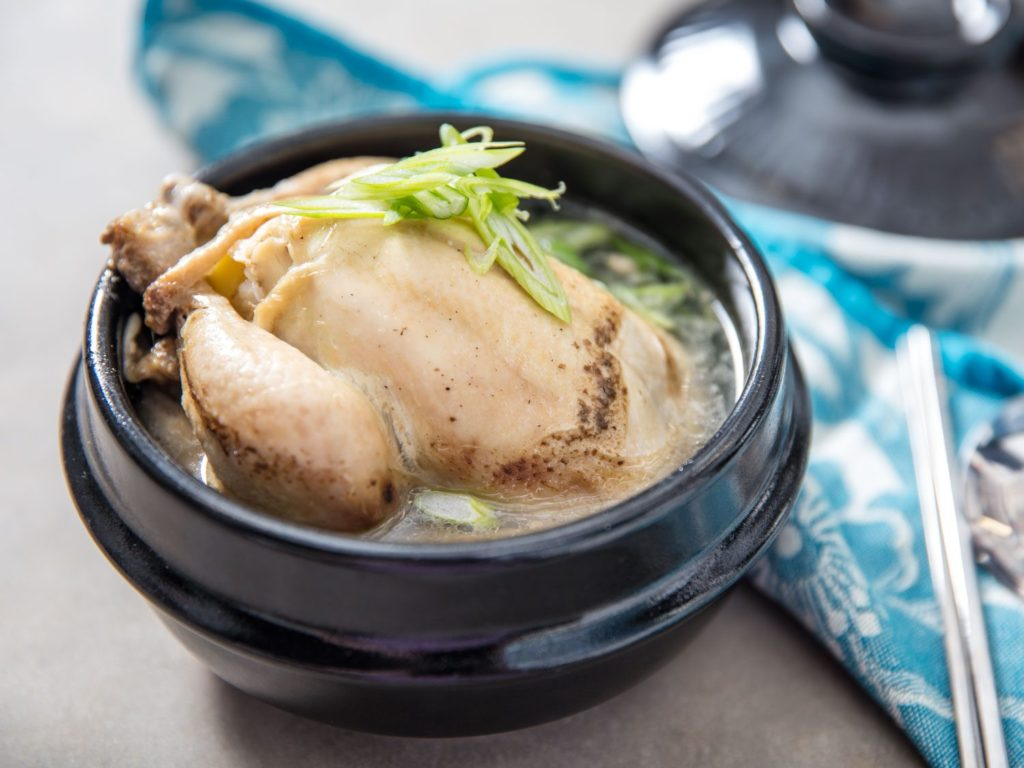 A whole chicken in a bowl of samgyetang, a traditional Korean dish