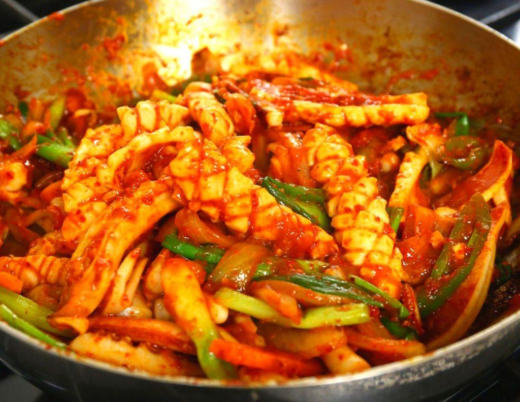 Ojingeo Bokkeum being stir fried in a wok in South Korea