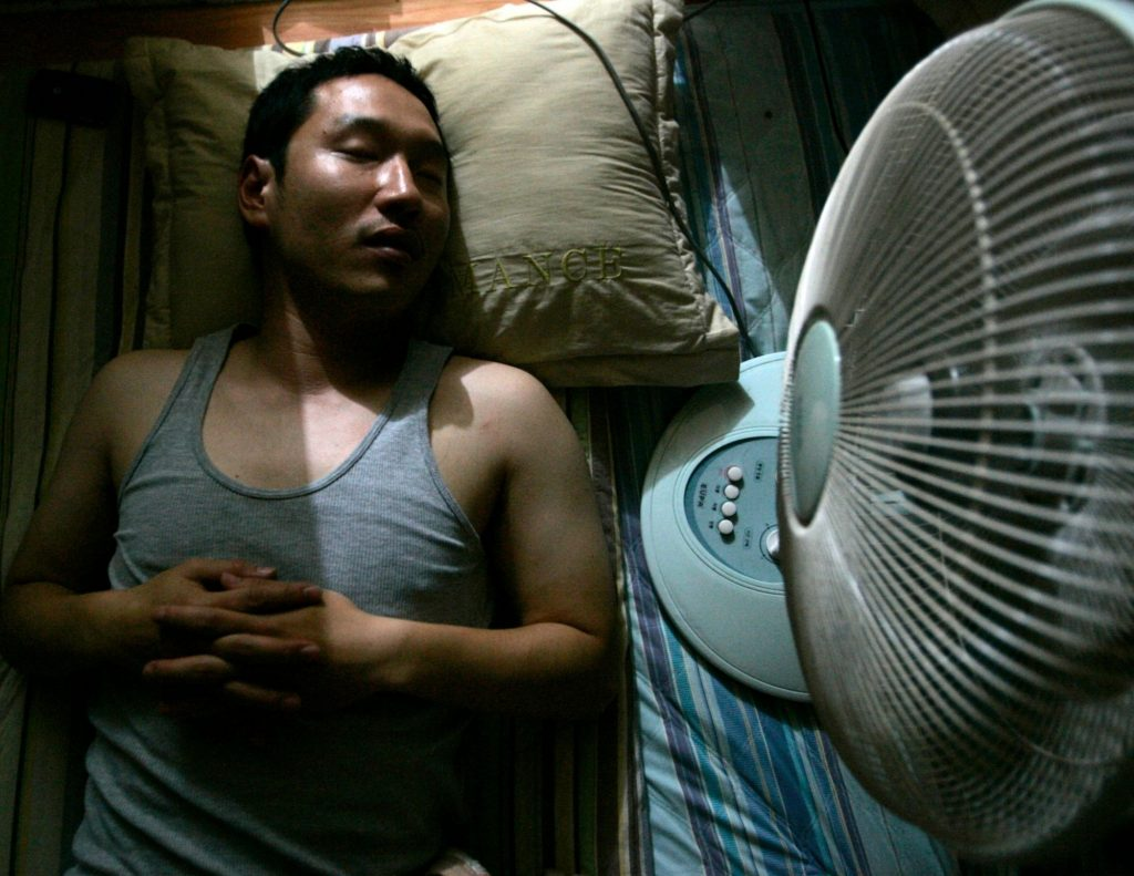 Man sleeping next to an electric fan